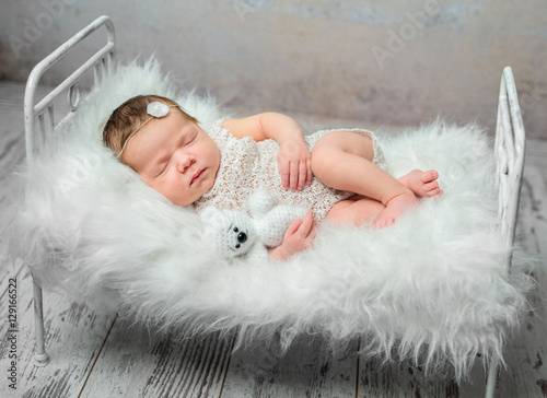 d41450c45 lovely baby in yellow romper sleeping with legs crossed