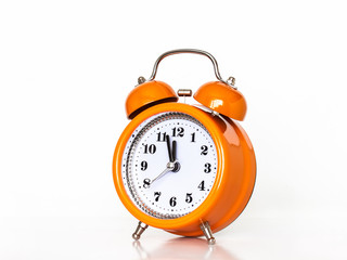 Orange alarm clock with hands showing midnight
