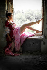 Beautiful Young Woman in Victorian Dress sitting on the Window in a Dark Room. Fairy Tale. Sun Light Effect