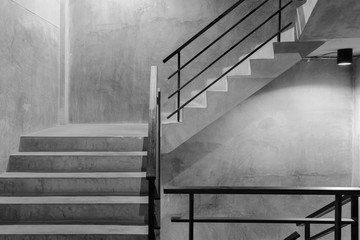 Empty modern rough concrete stairway with black steel handrail