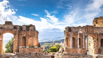 Ruins and columns of antique greek theater in Taormina and Etna Mount in the background. Sicily, Italy, Europe.