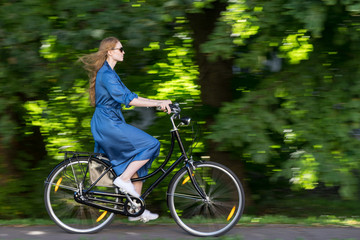 Beautiful young woman and vintage bicycle, summer. Red hair girl riding the old black retro bike outside in the park. Having fun in the city