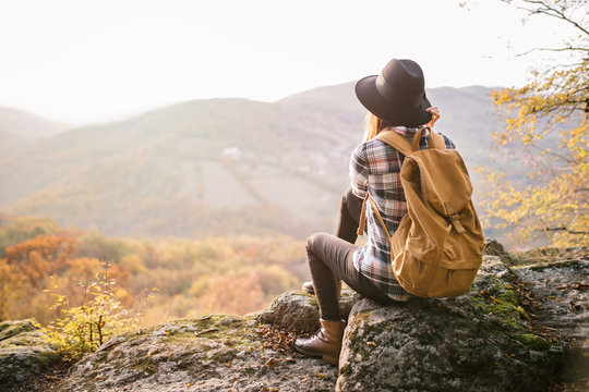 Young travel girl sitting at viewpoint. Hipster girl with backpack