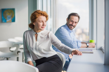 Businessman and businesswoman working in office interior all together. Happy people having break during work. Handsome man looking at his red haired colleague.