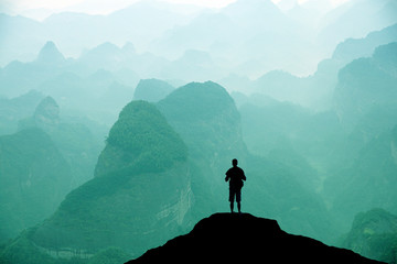 Climber standing the top of mountain in sunset background.  Wall mural