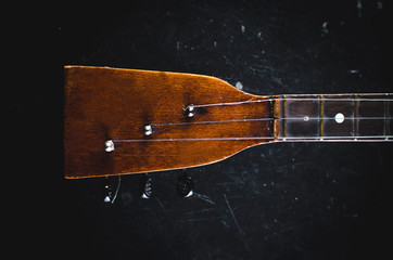 The neck of the guitar on a black
