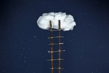 Largas escaleras de madera que llegan hasta una nube solitaria en medio del cielo estrellado de noche.