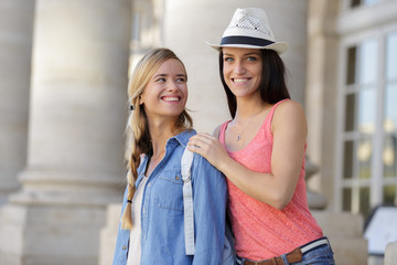 happy girlfriends walking through town during vacation