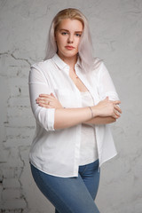 Portrait of a pretty big blonde in a white shirt on a gray background.