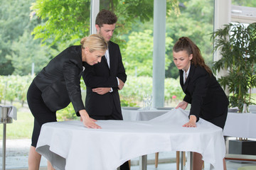 Trainee waiters learning how to set table