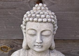 Head of Buddha on grey wooden background.