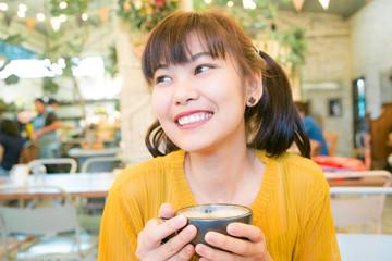 Smiling asian women sitting in art coffee shop