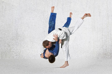 Two judokas fighters fighting men on gray