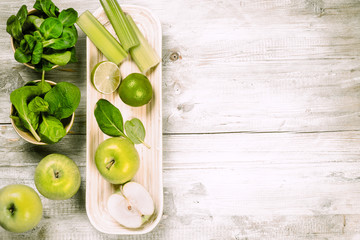 Fresh green vegetables and fruits on wooden background. Detox an