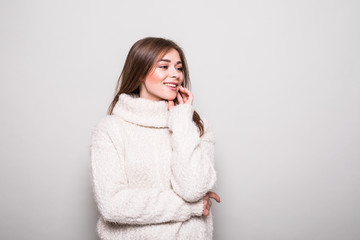 Pretty model in sweater in studio isolated gray background
