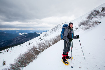Man hiking in winter mountains before thunderstorm