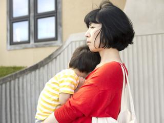 親子 眠る子供を抱っこする母親