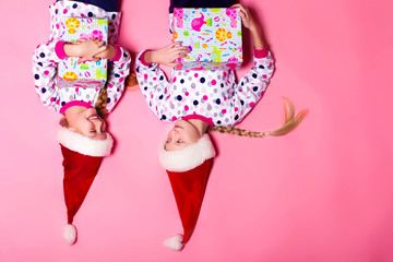 Two sisters lying on the floor on a pink background in pajamas