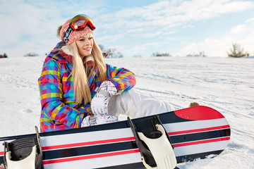Beautiful girl sitting with snowboard at the top of a mountain