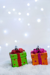 Christmas presents in snow with lights bokeh in background