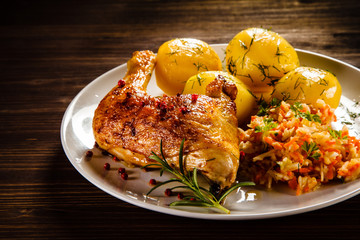 Grilled chicken leg with boiled potatoes and vegetable salad