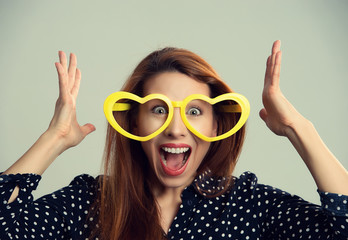 Woman with heart shaped party glasses happy surprised hands in the air