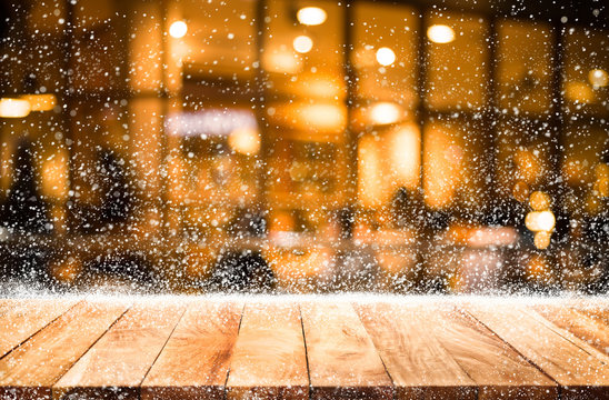Empty wood table top with snowfall and bokeh cafe restaurant in winter