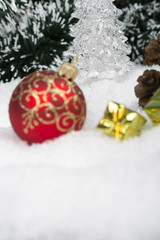 Christmas background with a red and blue ornament, golden gift box, Angels, berries and fir in snow on forest backround