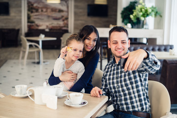 family, parenthood, technology people concept - happy mother, father and little girl having dinner taking selfie by smartphone at restaurant