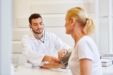 Arzt misst den Blutdruck einer Patientin