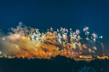"Fireworks over the city of St. Petersburg (Russia) on the feast of ""Scarlet Sails"", in the rain with fog and smoke."