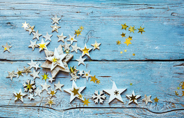 Christmas card with golden and wooden stars on an old blue board :)