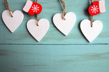 Decorative white wooden Christmas hearts and red mittens on blue wooden background with copy space.Selective focus.Winter holidays,Merry Christmas or Happy New Year concept.