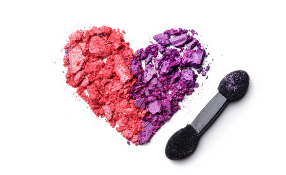crushed heart of eye shadows and brush isolated