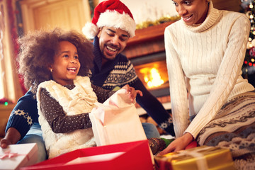 Happy Afro-American family opening Christmas presents.