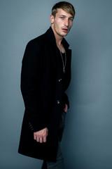 handsome young man in black jacket posing in studio