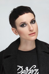 Pretty young woman with short black hair in warm coat. Haircut and style, natural makeup.