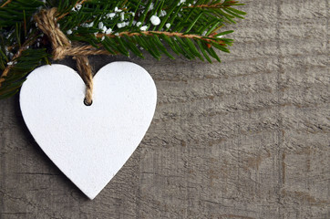 Decorative white wooden Christmas heart on grey rustic wooden background with copy space.Selective focus.Winter holidays,Merry Christmas or Happy New Year concept.