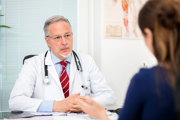 Doctor talking to a patient in his studio