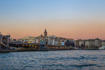 Sunset view of Galata tower and Galata bridge over the Bosphorus channel, Istanbul, Turkey