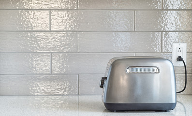 Plugged in retro styled toaster with sliced bread against cerami