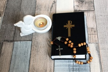 Catholic rosary beads with prayer book and angel candle. Religious background.
