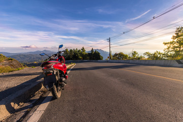 Motorcycle, serpentine road, mountains on background and blue sky on sunset. Active lifestyle and vacation concept.