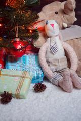 Various Christmas presents under the illuminated tree