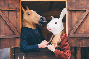Couple of young beautiful  millennial woman and man wearing horse and rabbit mask standing on the window of a wooden house - carnival, strange concept