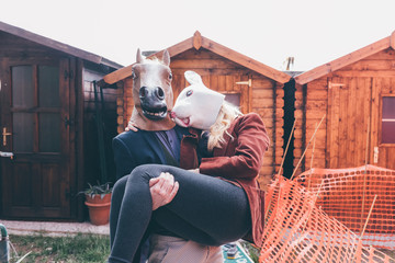 Couple of young beautiful redhead and blonde millennial woman and man wearing horse and rabbit mask, he is holding her outside their home - married, couple concept