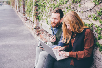 Couple of young beautiful redhead and blonde millennial woman and man colleague outdoor in the city using computer and tablet - business, technology, social network concept