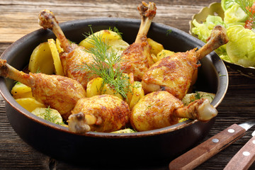 Chicken legs and baked dill potatoes with vegetable salad