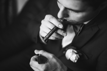 the groom in a suit smoking cigar