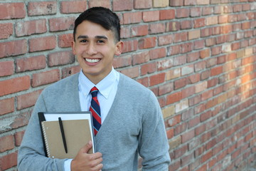 Cute teenager boy in formal high school uniform holding notebooks smiling with copy space